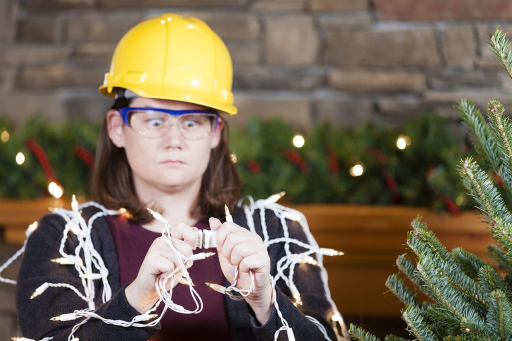 Young woman wearing hardhat and safety glasses plugging in Christmas tree lights